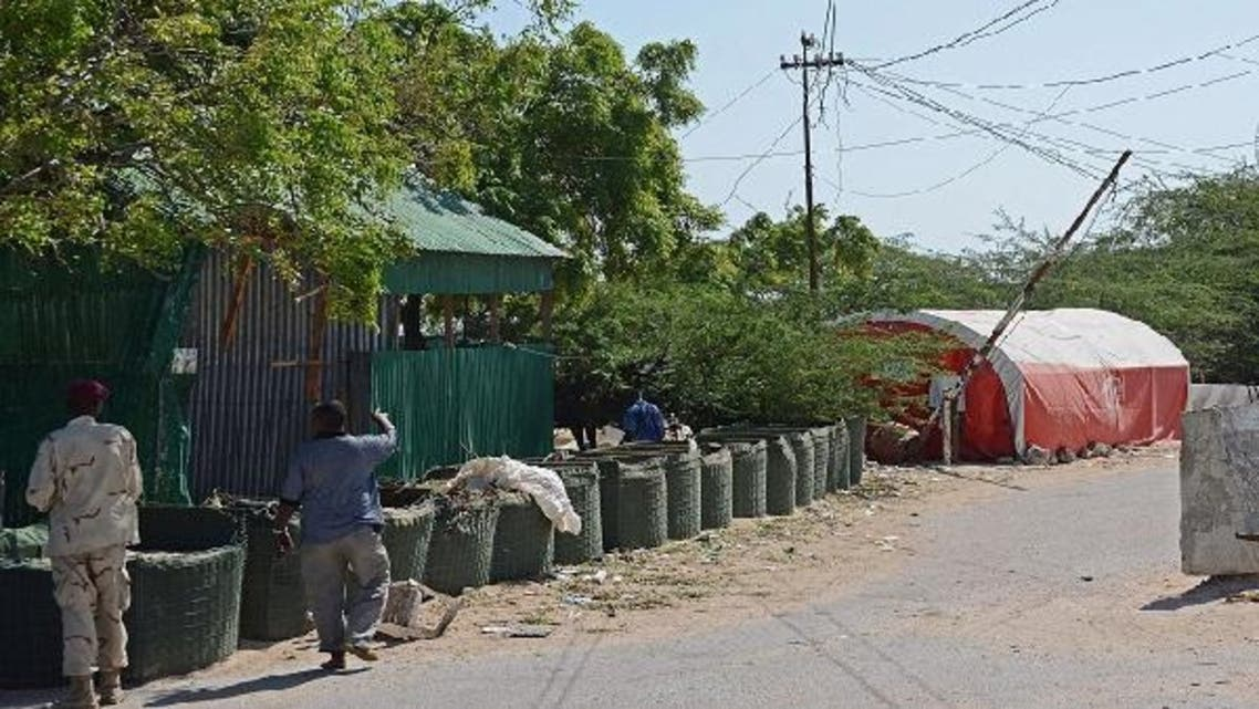 People walk past the presidential palace in Mogadishu after a suicide bomber blew himself up. (AFP)