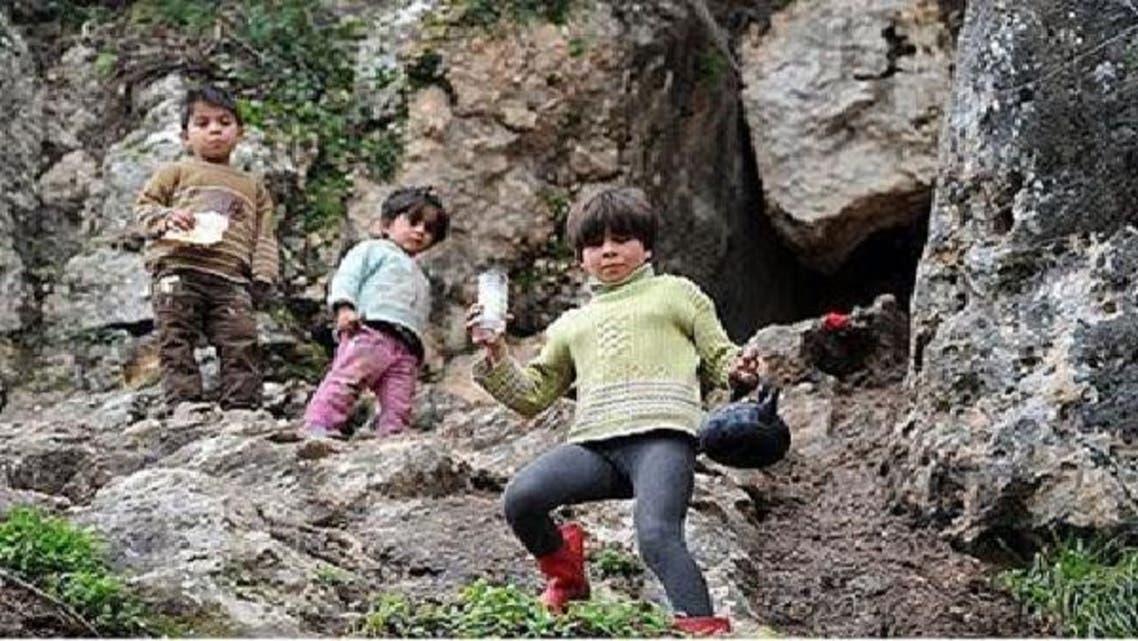 أطفال سوريون أمام أحد الكهوف الجبلية بمنطقة عين الزرقا