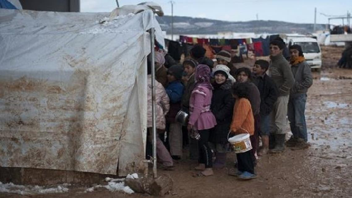 Syrian refugee children wait in freezing conditions for their families daily rations of food at a refugee camp in Bab al-Salam on the Syria-Turkey border, on Jan. 9, 2013. (AFP)