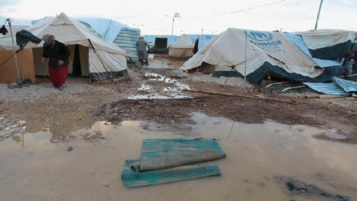 Syrian refugees fix their tents after heavy rain at Al-Zaatari refugee camp in the Jordanian city of Mafraq, near the border with Syria, January 10, 2013. (Reuters)