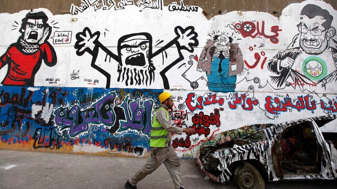 A worker walks past a graffiti denouncing Egypt's President Mohamed Mursi and representing the Muslim Brotherhood along Mohamed Mahmoud street near Tahrir Square in Cairo February 13, 2013. (Reuters)