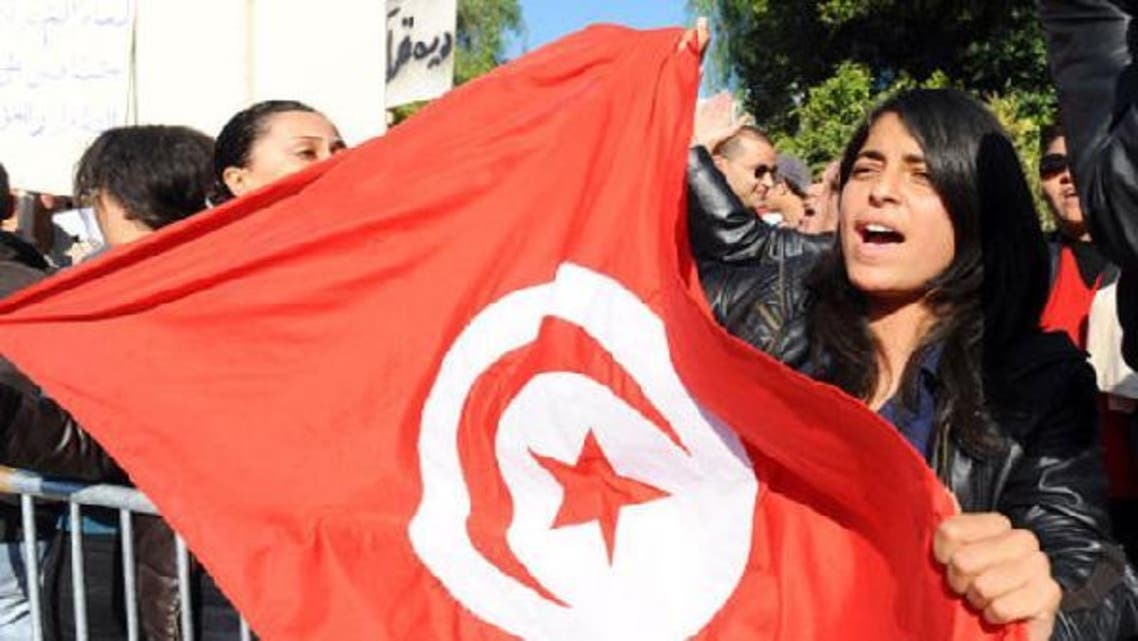 A Tunisian woman holds a flag of Tunisia during a demonstration in front of the assembly in Tunis last December. (AFP)