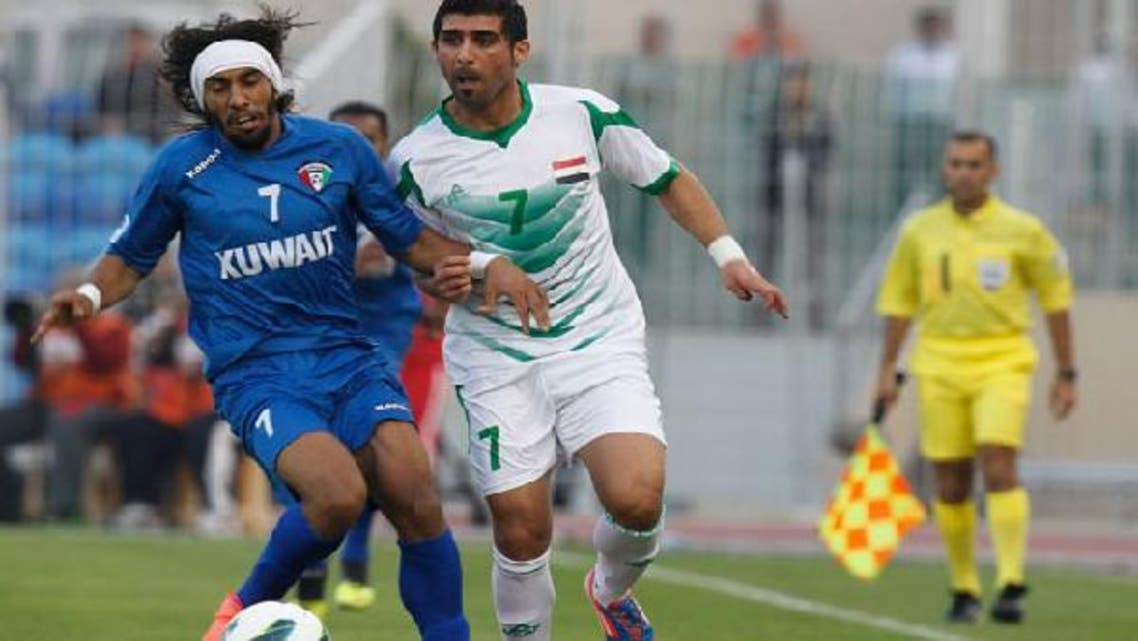 Iraq's Hammadi Ahmed Abdullah (R) and Kuwait's Fahad Al Enezi fight for the ball during their Gulf Cup tournament soccer match at Khalifa Sports City in Isa Town January 9, 2013.  (Reuters)