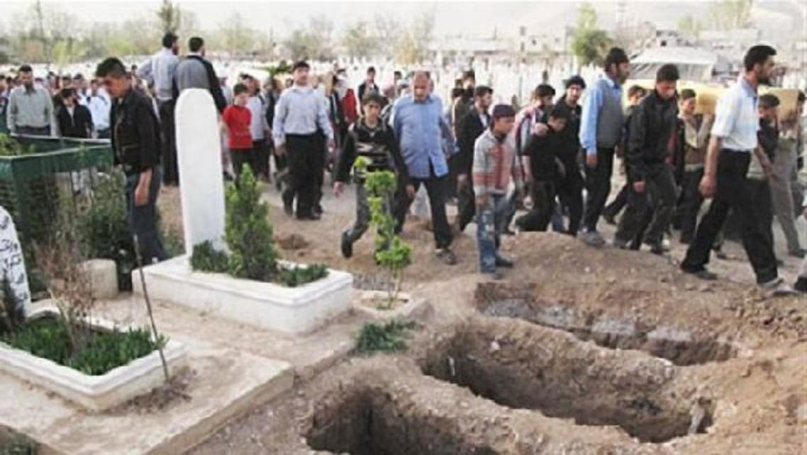 Mourners walk past open graves at a cemetery during the funeral for four people killed in a raid by government forces in a neighborhood of Damascus last year. (Courtesy: AP)