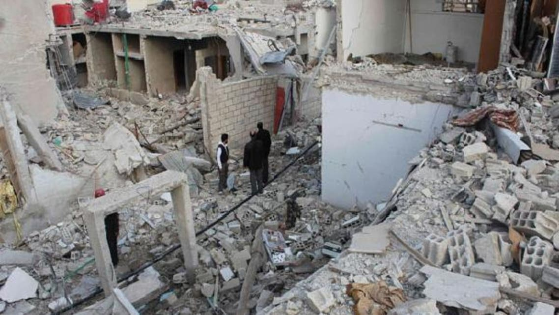 Residents stand near buildings damaged by what activists said were missiles fired by a Syrian Air Force fighter jet of forces loyal to Syria's President Bashar al-Assad at Douma near Damascus December 17, 2012. (Reuters)