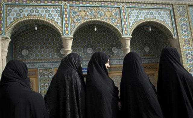 Veiled Iranian women wait in a queue to vote at a polling station in Qom during parliamentary elections on March 2, 2012. (AFP)