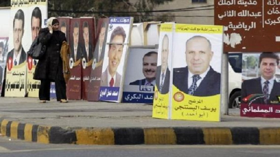 A Jordanian woman walks past pictures of parliament candidates in Amman on Dec. 29, 2012. (AFP)