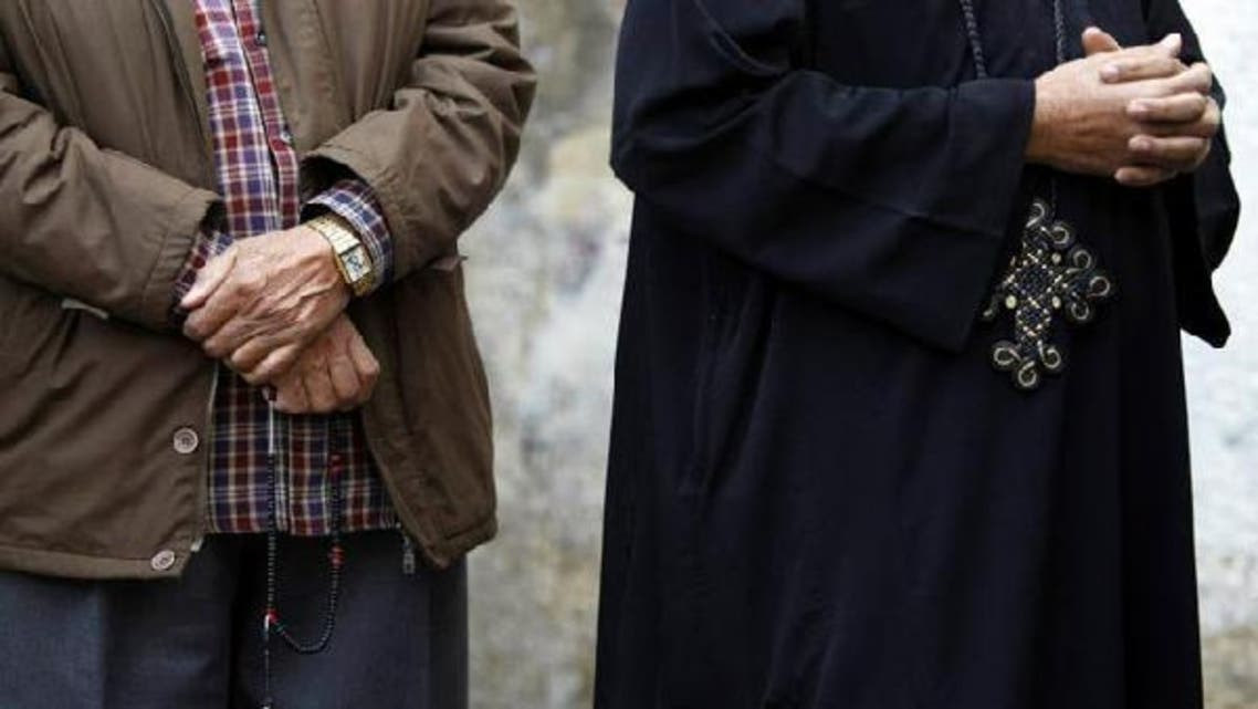 A Muslim Egyptian man holding prayer beads stands next to a Coptic Christian wearing a cross as they queue outside a polling center. (Reuters)