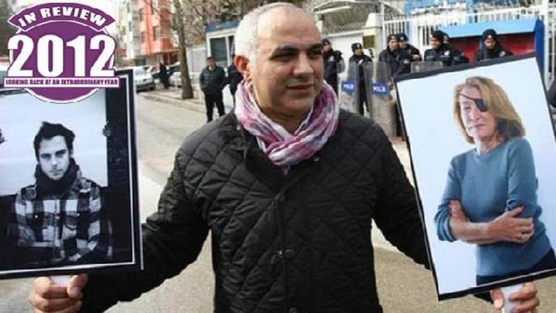 A Turkish journalist in Ankara, on Feb 24, 2012 holds pictures of two journalists, French photojournalist Remi Ochlik (L) and Sunday Times correspondent Marie Colvin, killed in an alleged rocket attack by Syrian regime forces. (AFP)