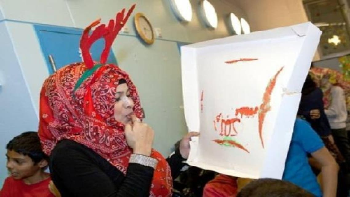 A Muslim mum gets into the Christmas spirit with reindeer head gear, while others at the party tuck into traditional Christmas pudding.(Coutesy:East London Advertiser)