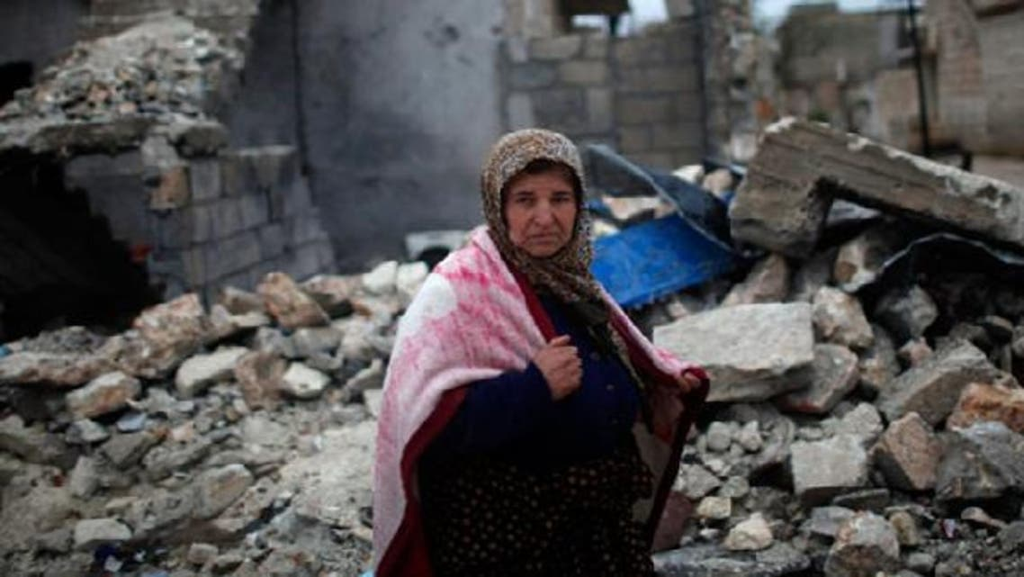 A woman walks past a house destroyed by an airstrike by Syrian government forces two days ago according to local residents in Azaz city December 18, 2012. (Reuters)
