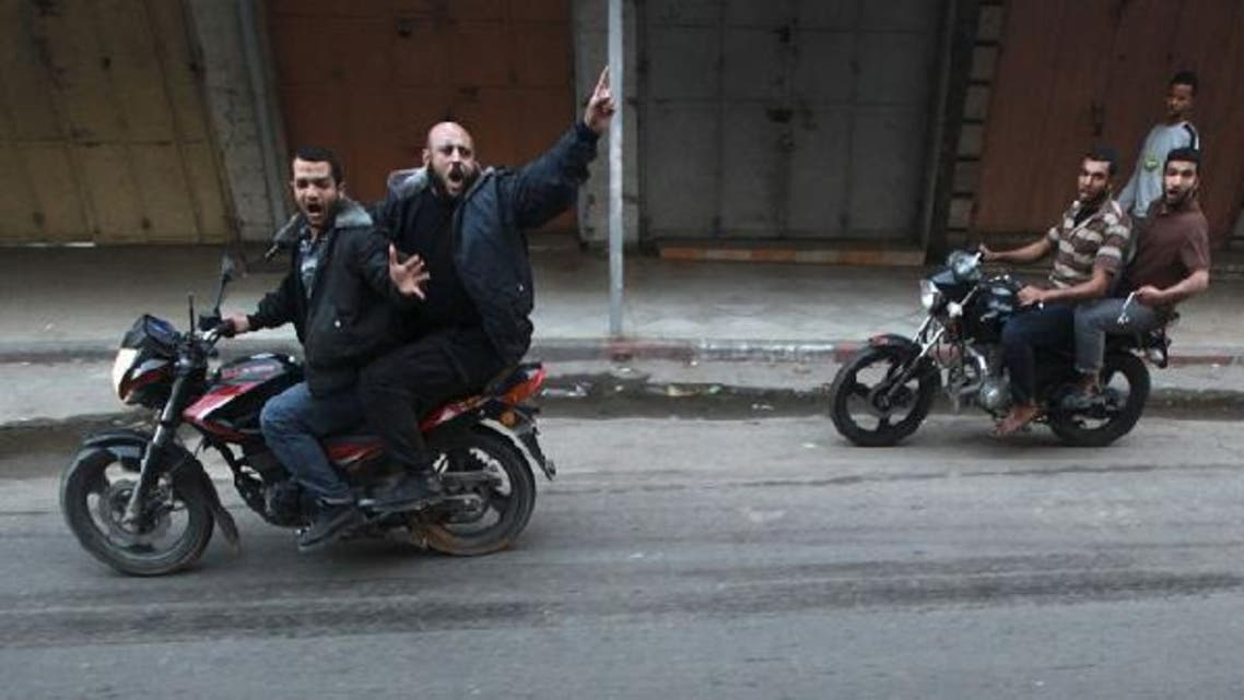 Palestinian gunmen ride motorcycles as the body of a man, who was suspected of working for Israel, was dragged through the streets of Gaza City on Tuesday. (Reuters)