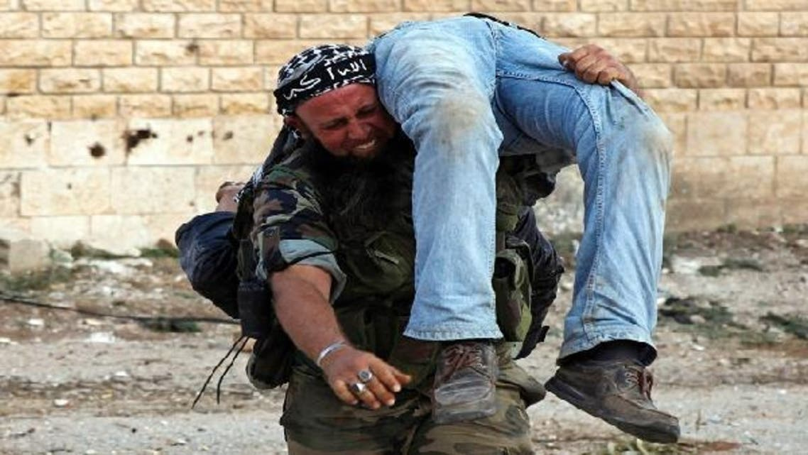 A Free Syrian Army fighter reacts as he carries the body of a fellow fighter after he was killed by a sniper loyal to Syria\'s President Bashar al-Assad in Khan al-Assal area. (Reuters)