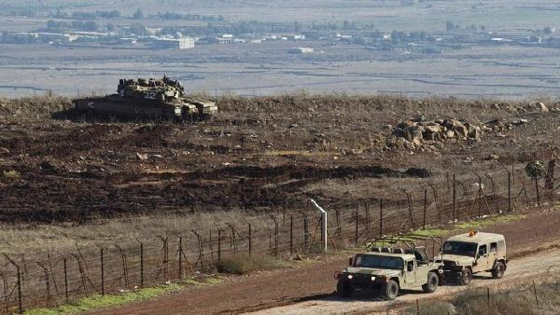An Israeli military vehicle tows another as a tank stands in position close to the ceasefire line between Syria on the Israeli-occupied Golan Heights. (Reuters)