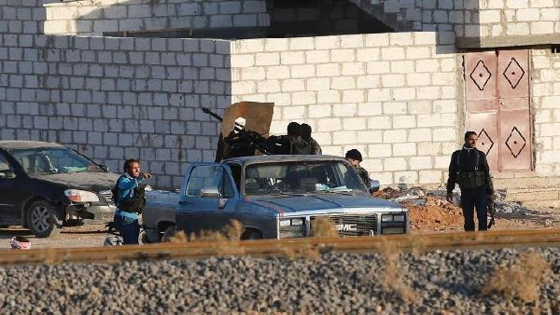 Free Syrian Army fighters surround a truck on which a weapon is mounted in the Syrian town of Ras al-Ain, as seen from the Turkish border town of Ceylanpinar, Sanliurfa province. Syrian warplanes bombed the rebel-held town of Ras al-Ain on Monday, just meters from the Turkish frontier, sending scores of civilians fleeing for safety into Turkey. Helicopters also strafed targets near the town, which fell to rebels on Thursday during an advance into Syria\'s mixed Arab and Kurdish northeast. (REUTERS)