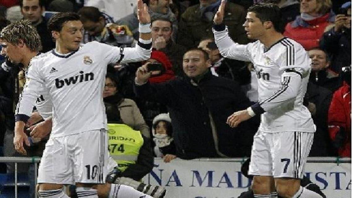 أوزيل يهنئ رونالدو بعد تسجيله هدف فريقه الأول في مرمى اتليتكو مدريد