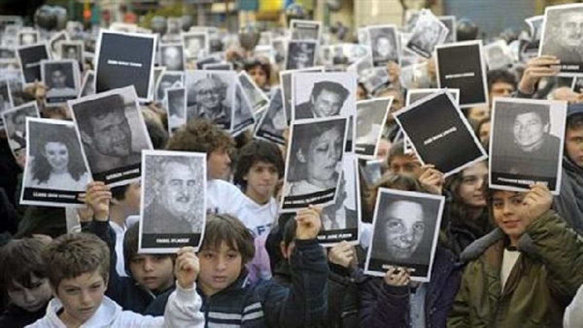 People hold portraits of victims of the terrorist bombing attack against the Argentine Israelite Mutual Association (Amia). (AFP)