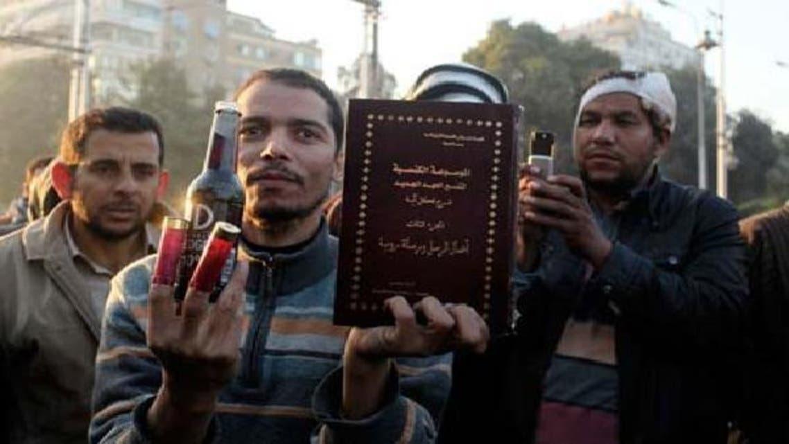 قاہرہ میں اخوان المسلمون کا ایک حامی حزب اختلاف کے مظاہرین کی جانب سے چلائے گئے کارتوسوں کے خول اور شراب کی بوتل دکھا رہا ہے