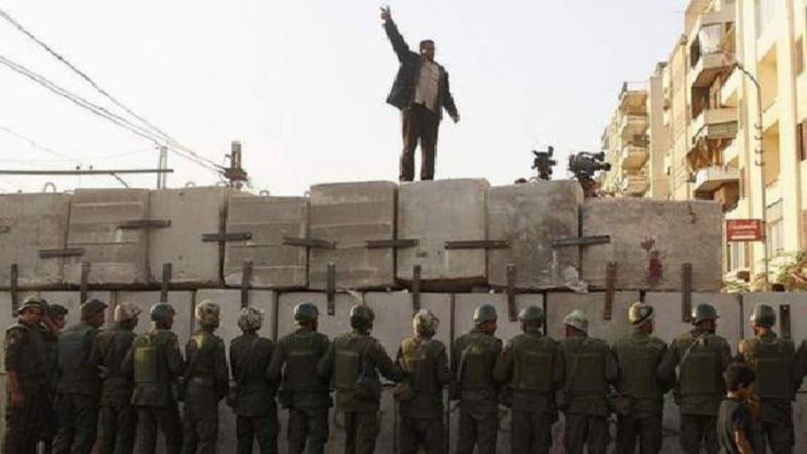 قاہرہ میں صدارتی محل کےباہر حزب اختلاف کا ایک کارکن نئے بنائے گئے بیرئیر کے اوپر چڑھ کر نعرے بازی کر رہا ہے