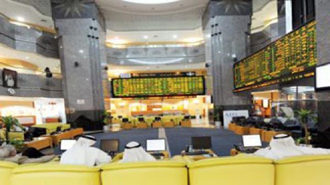 متعاملون يتابعون شاشة التداول في سوق أبوظبي للأوراق المالية