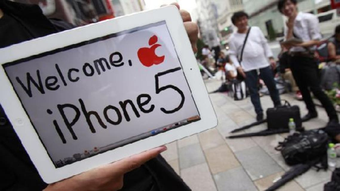 People wait in line to buy Apple Inc\'s iPhone 5 as an Apple fan shows his iPad outside Apple Store in Tokyo\'s Ginza district. (Reuters)