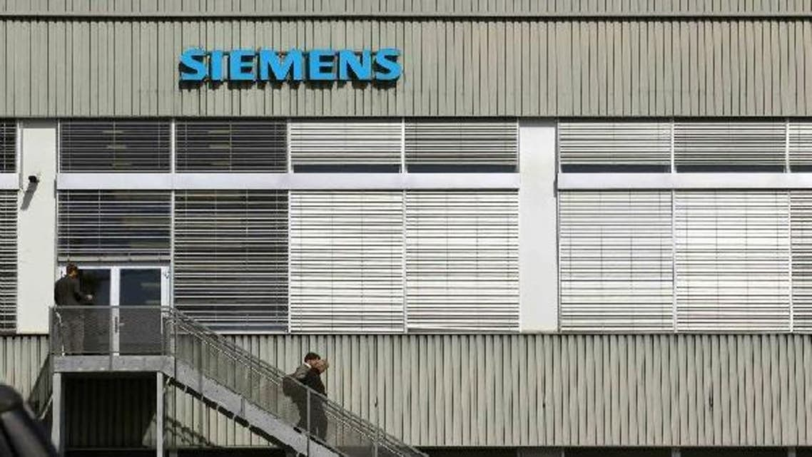 People walk down stairs in front of a building of Siemens Schweiz AG Building Technologies Group, a Swiss unit of German Siemens AG in the central Swiss town of Zug September 20, 2012. (Reuters)