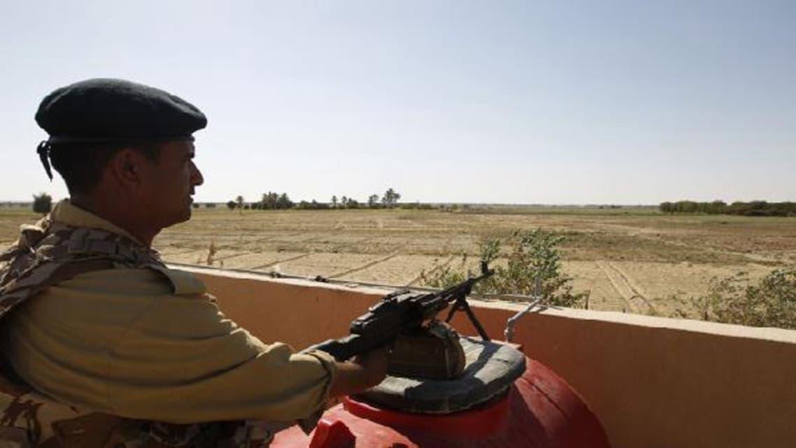 An Iraqi border policeman mans a machine gun near the Iraqi-Syrian borders at the Albu Kamal-Qaim border crossing, the main border post between Iraq and Syria. (Reuters)