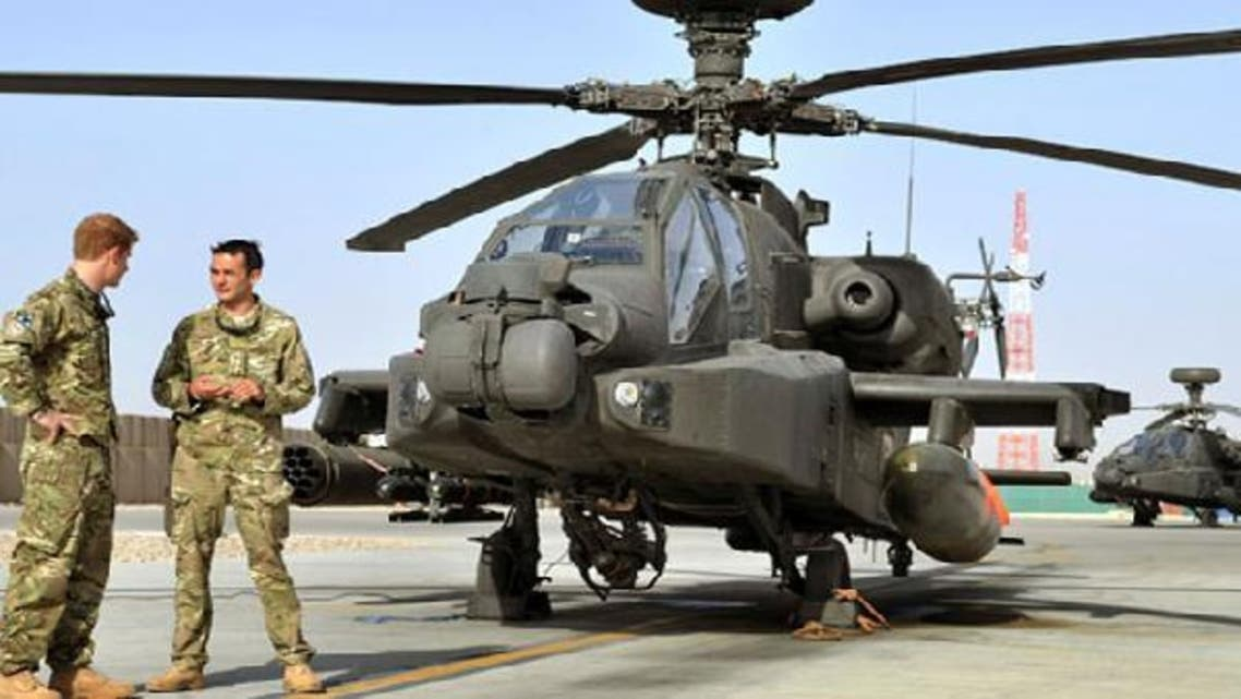 Britain's Prince Harry is shown the Apache helicopter flight line by an unidentified member of his squadron at Camp Bastion, Afghanistan. Six U.S. fighter jets were destroyed at Camp Bastion by the Taliban on Friday, NATO said. (Reuters)