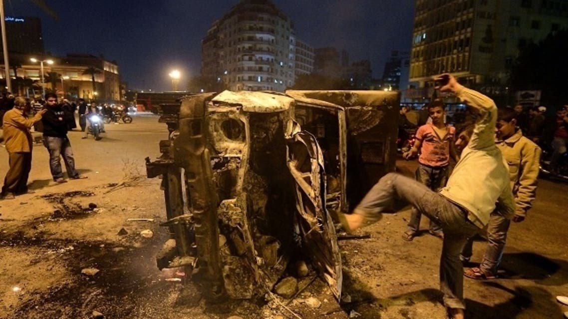 An Egyptian man gives a kick towards a police vehicle that has been burnt by angry protesters following clashes with plainclothes policemen in Cairo's on Tahrir square on March 3, 2013. (AFP)