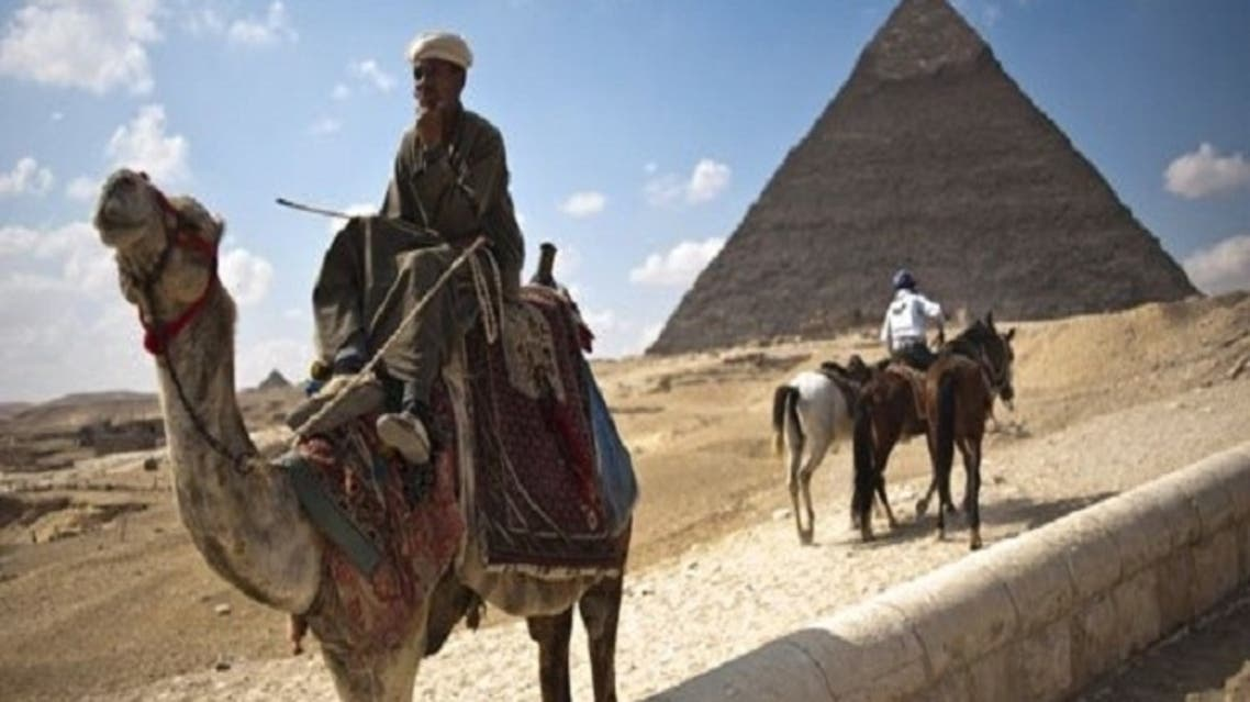 An Egyptian man waits for tourists to take them on camel rides at the Giza pyramids on the outskirts of Cairo. The country's economy has taken a huge dip after foreign tourists fled during Egypt's uprising. (AFP)
