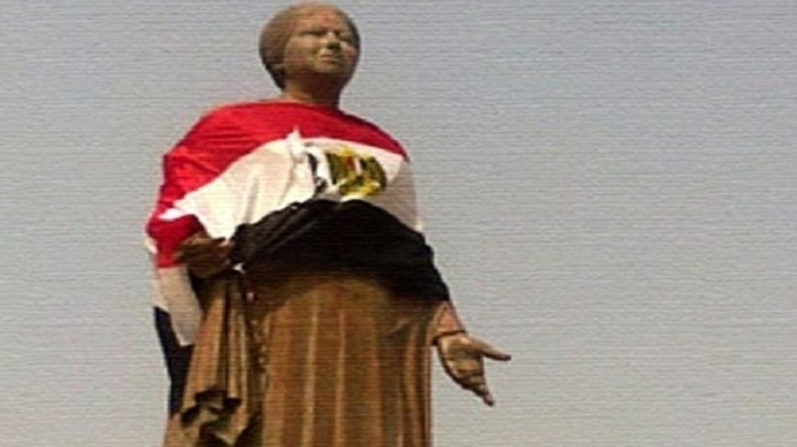 A picture of Umm Kolthoum's statue after activists cleaned it and painted its base, then wrapped the statue with the Egyptian flag to mark the singer's patriotism. (Al Arabiya)