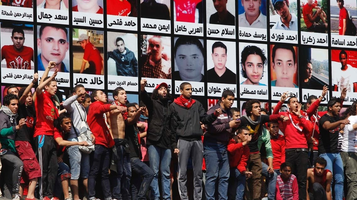"Abd El Monaem ""Kabo"" (C, in cap) leader of Al-Ahly fans who are also known as ""Ultras"" shouts slogans in front of the Al-Ahly club after hearing the final verdict of the 2012 Port Said massacre in Cairo March 9, 2013."