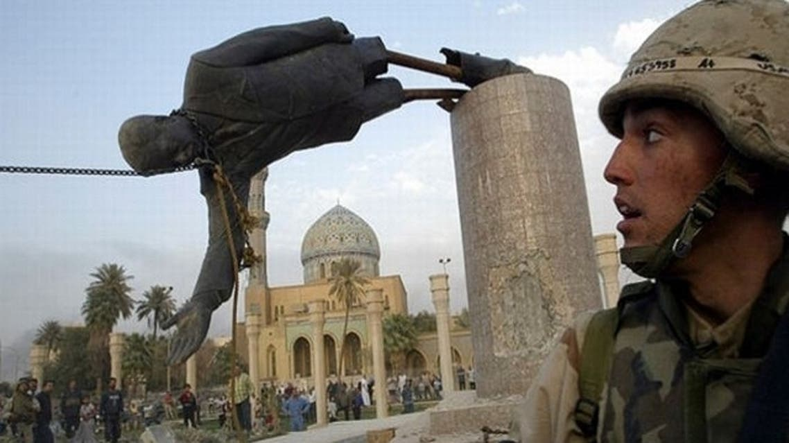 U.S. Marine watches as a statue of Iraq's President Saddam Hussein falls in central Baghdad on April 9, 2003. (Reuters)