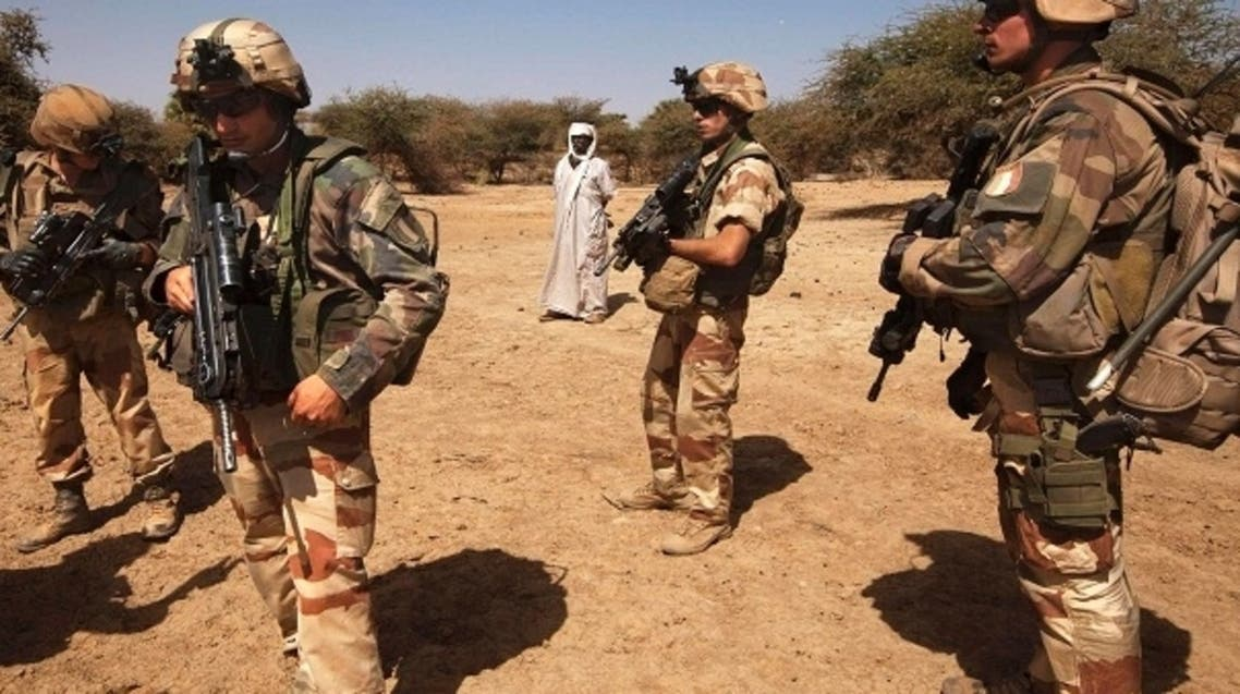French soldiers stand guard next to a local resident outside Gao, Mali, March 9 2013. (Reuters)