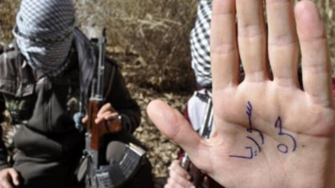 """An Iraqi gunman, a member of the """"Army of Free Iraqis"""", shows his palm reading """"Free Syria"""" in a field in the western town of Al-Qaim close to Iraq's border with Syria (AFP Photo / Azhar Shallal)"""