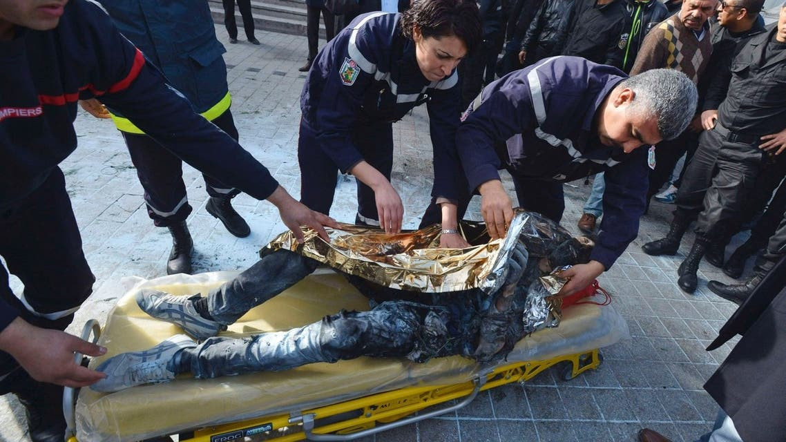 The body of a young Tunisian man, who set himself on fire, is placed on a stretcher before transporting it into an ambulance in the main street of the capital Tunis March 12, 2013. (Reuters)