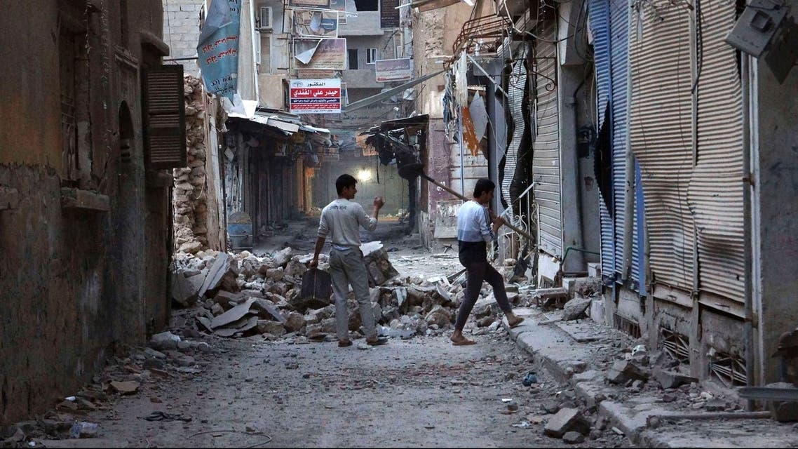 Men clear debris from one of the buildings in Deir al-Zor March 12, 2013. (Reuters)