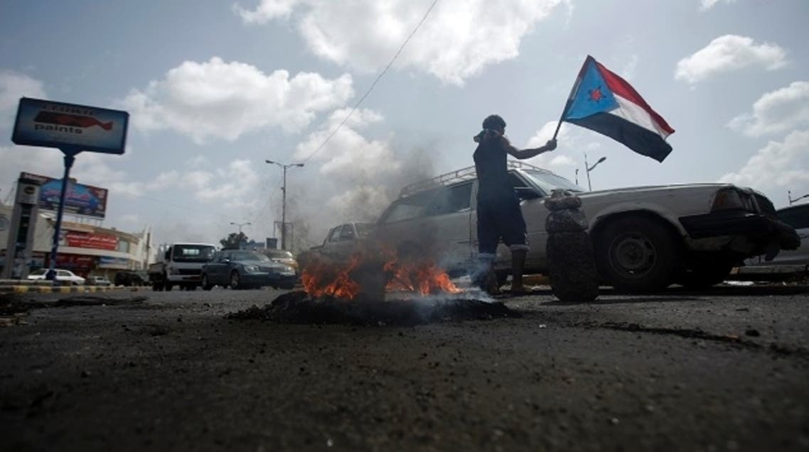 A follower of the separatist Southern Movement holds a flag of former South Yemen as he stops cars on a street in the southern Yemeni port city of Aden February 26, 2013. (Reuters)