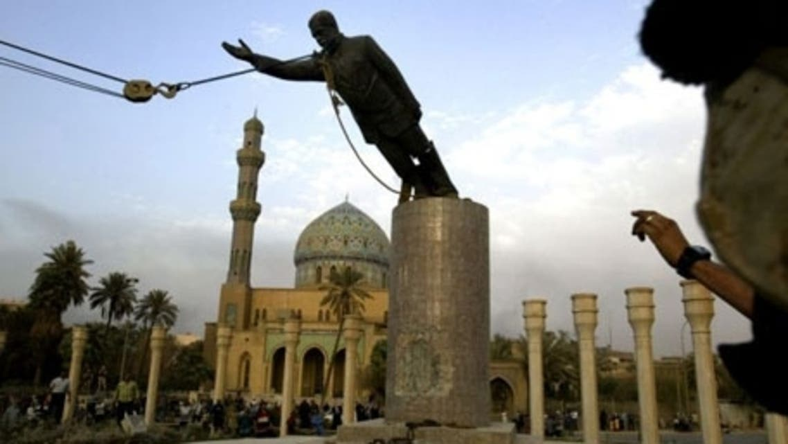 A U.S. marine watches a statue of Saddam Hussein being toppled in Baghdad on 9 April 2003. (AP)