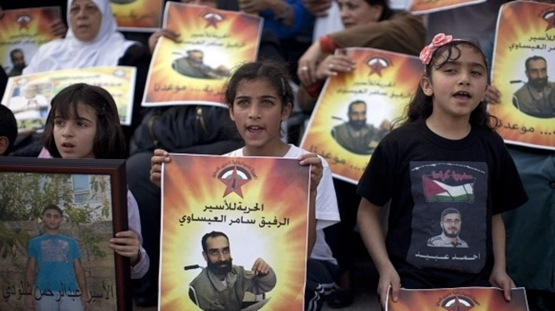 Young Palestinian protesters hold portraits of Samer Issawi, a Palestinian prisoner who has been on a hunger strike for more than 200 days, during a solidarity sit-in outside the Red Cross offices in Jerusalem on March 14, 2013. (AFP)