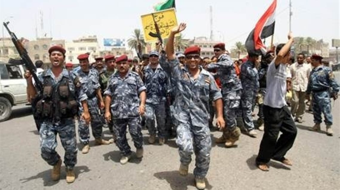 police and soldiers celebrate in the southern city of Basra on Tuesday after U.S. troops withdrew from towns and cities across the country.