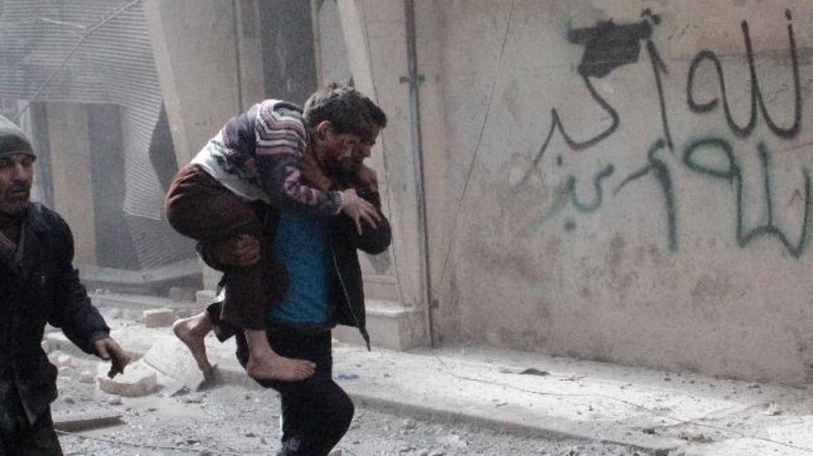 """A man carries a child who was wounded after a jet missile hit the al-Myassar neighborhood of Aleppo February 20, 2013. The Arabic graffiti on the wall reads, """"God is great"""". (Reuters)"""