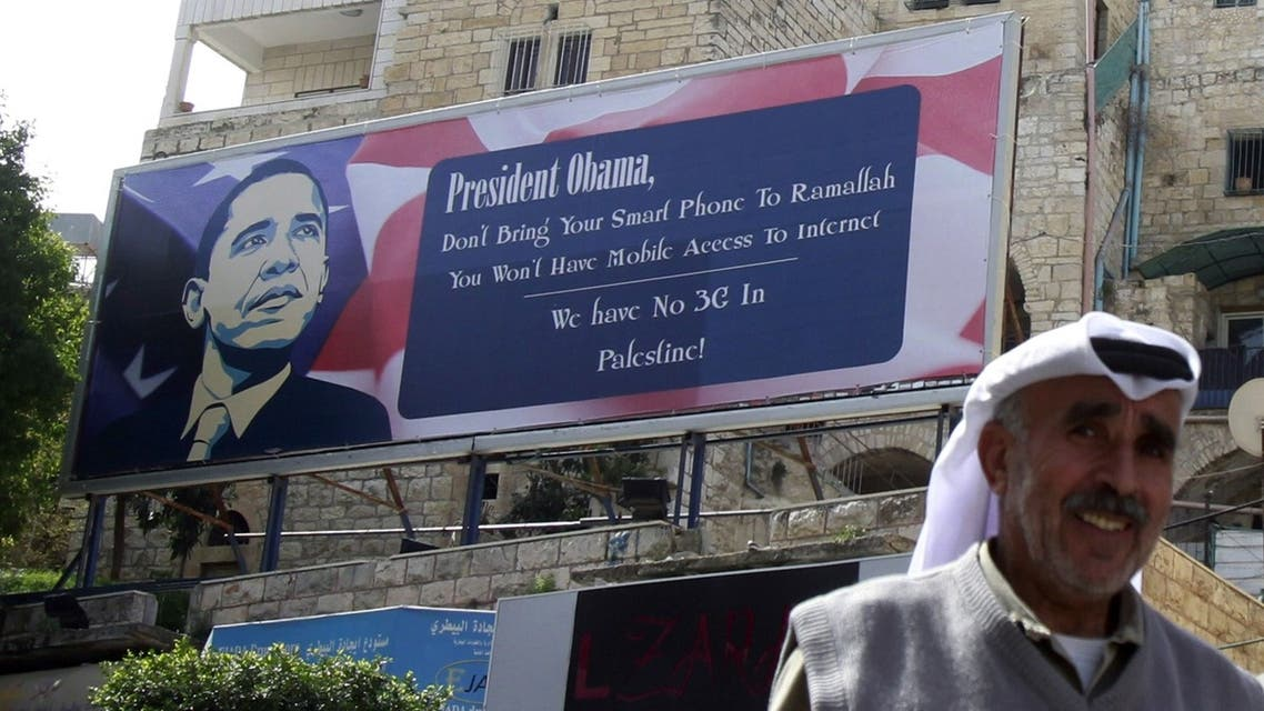 A Palestinian man walks past a poster depicting U.S. President Barack Obama in the West Bank city of Bethlehem on March 16, 2013. (AFP)