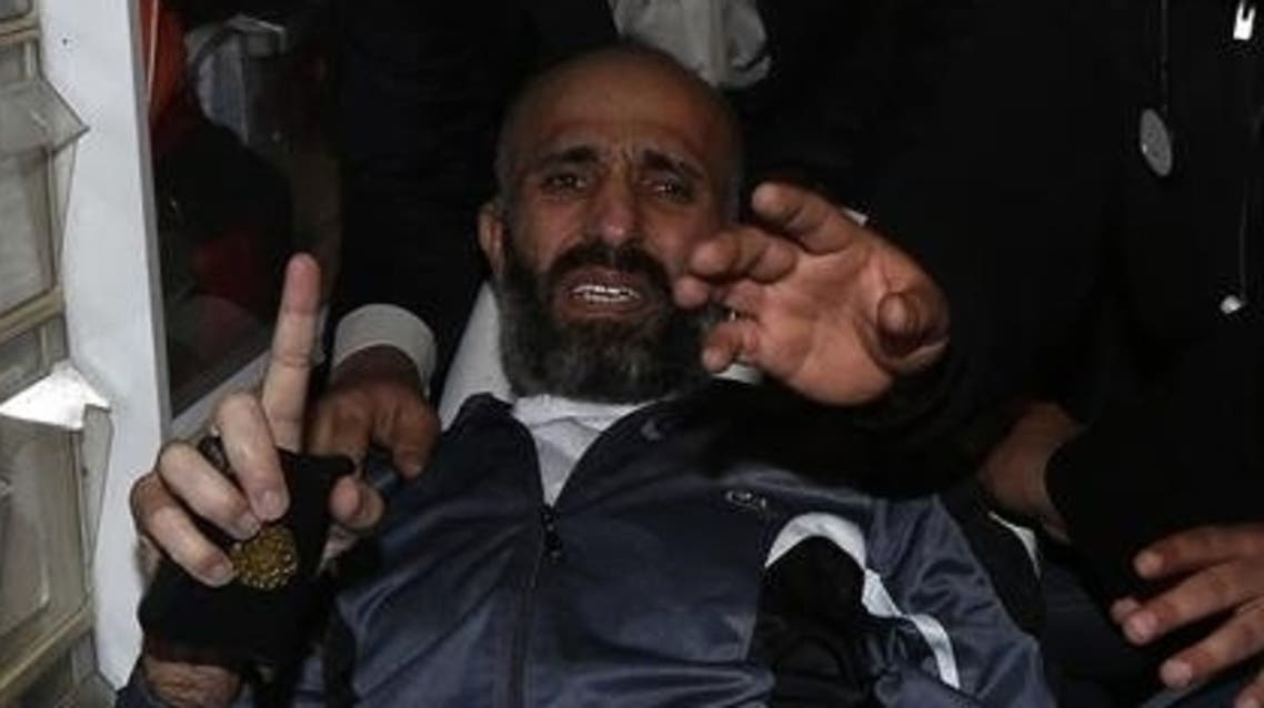 Freed Palestinian prisoner Ayman Sharawneh gestures as he holds a copy of the Koran inside an ambulance upon his arrival near Erez crossing in the northern Gaza Strip March 17, 2013. (Reuters)