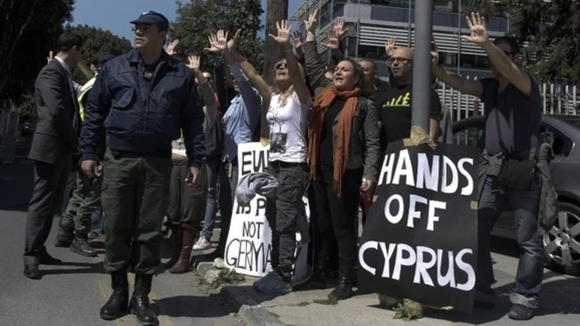 Demonstrators raise arms as the convoy of the Cypriot President drives to the Parliament (Reuters)