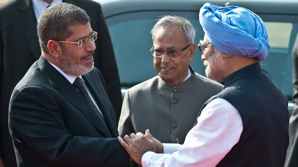 Indian President Pranab Mukherjee (C) watches as Egyptian President Mohamed Morsi (L) shakes hands with Indian Prime Minister Manmohan Singh during a ceremonial reception at the president's house in New Delhi on March 19, 2013.