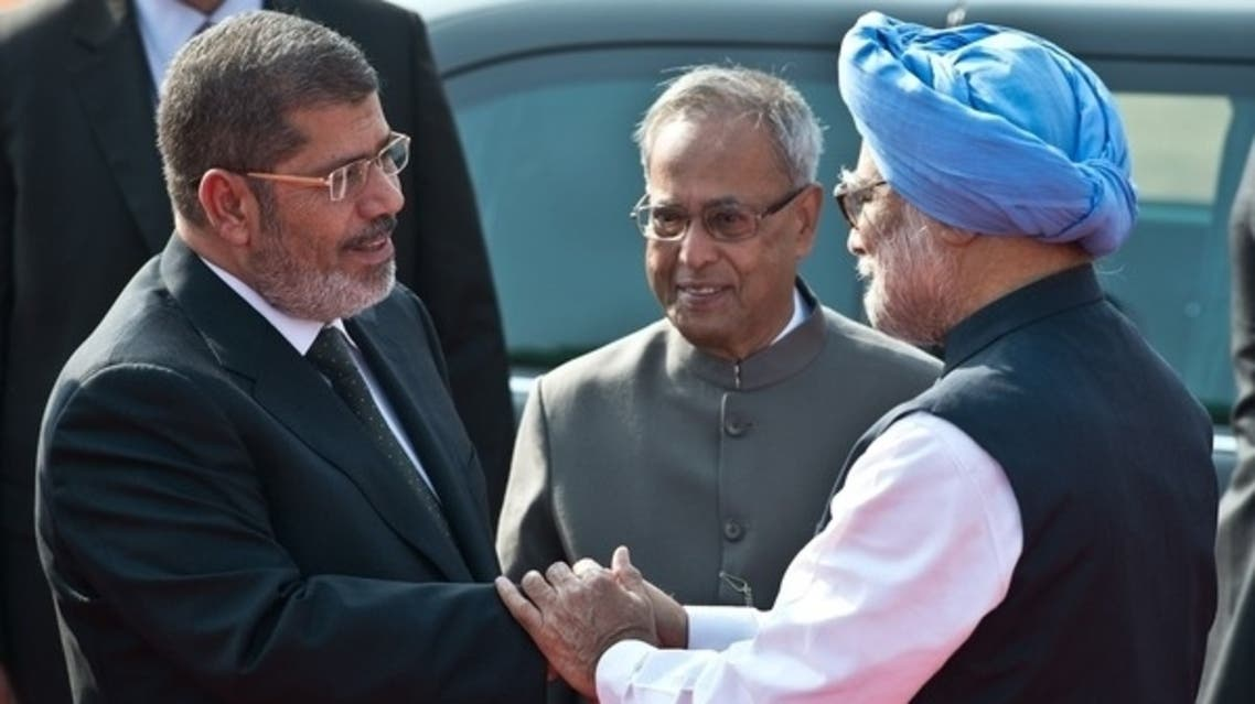 Indian President Pranab Mukherjee (C) watches as Egyptian President Mohamed Morsi (L) shakes hands with Indian Prime Minister Manmohan Singh during a ceremonial reception at the president's house in New Delhi on March 19, 2013. (AFP)