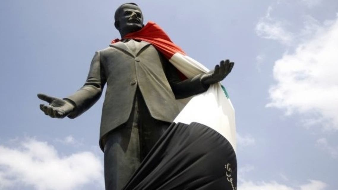 A Syrian flag hangs over a statue of the late president Hafez al-Assad on Aug. 30, 2011, near Homs. Alawites have ruled Syria since Hafez seized power in 1970.