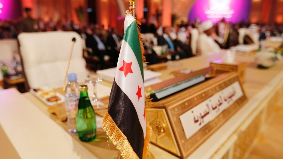 The Syrian opposition flag is seen in front of the seat of the Syrian delegation at the opening the Arab League summit in Doha March 26, 2013. (Reuters)