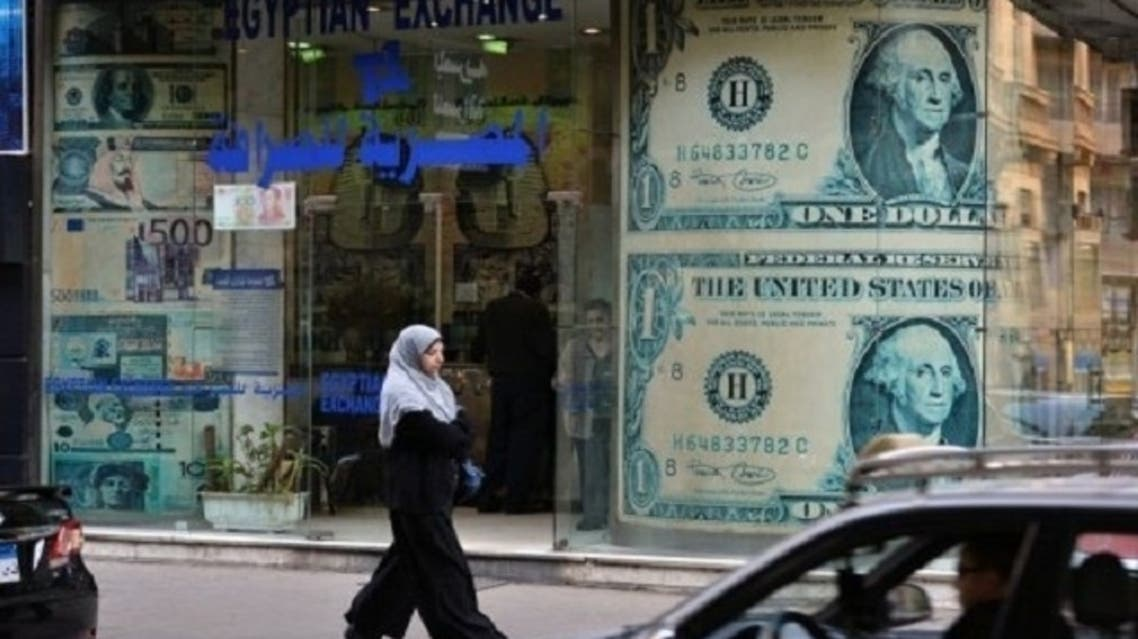 A woman walks past a foreign exchange store in Cairo on Sunday. After two years of political upheaval and weakness in the economy, companies in Egypt are struggling with a sinking currency. (AFP)